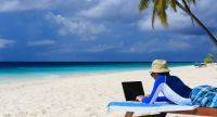 man with laptop on tropical vacation